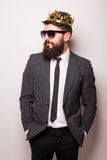 Young handsome man in sunglasses wearing suit and crown keeping hand on his jacket Royalty Free Stock Image