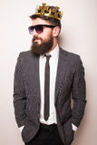 Young handsome man in sunglasses wearing suit and crown keeping hand on his jacket Royalty Free Stock Photography