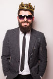 Young handsome man in sunglasses wearing suit and crown keeping hand on his jacket  while standing Stock Photography