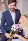 Young handsome man surprising her beautiful girlfriend and gives her bouquet of purple white flowers. Royalty Free Stock Images