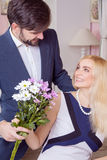 Young handsome man surprising her beautiful girlfriend and gives her bouquet of purple white flowers. Stock Photo