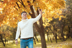 Young handsome man in sweater and jeans staying in autumn orange park smiling and waving to someone. Stock Photography