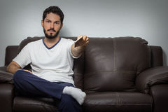 Young handsome man switching TV channel on a sofa at home. Royalty Free Stock Photos
