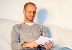 young handsome man with tablet relaxing on sofa stock image