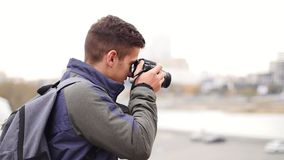 Young handsome man takes photo of the camera with own camera and smiles stock video footage