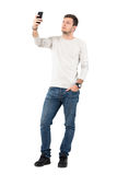 Young handsome man taking photo with cell phone. Full body length portrait isolated over white studio background Royalty Free Stock Image