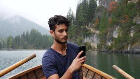Man taking photo at lake with smartphone. Young handsome man taking photo with smartphone at lake in forest, on a wood boat. Braies lake or Pragser Wildsee in stock video