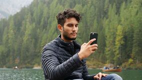 Man taking photo at lake with smartphone. Young handsome man taking photo with smartphone at lake in forest, on a wood boat. Braies lake or Pragser Wildsee in stock footage