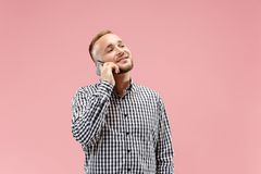 Young handsome man talking over phone and looking away. Young businessman using smartphone isolated on pink background. Smiling guy at cellphone stock images