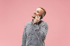 Young handsome man talking over phone and looking away. Young businessman using smartphone isolated on pink background. Smiling guy at cellphone royalty free stock photo