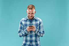 Young handsome man talking over phone and looking away. Young businessman using smartphone isolated on pink background. Smiling guy at cellphone stock photos