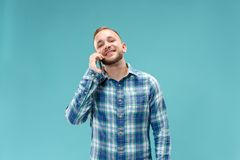 Young handsome man talking over phone and looking away. Young businessman using smartphone isolated on blue background. Smiling guy at cellphone royalty free stock image