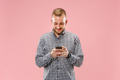 Young handsome man talking over phone and looking away. Young handsome man talking over phone and looking on it. Young businessman using smartphone isolated on royalty free stock image