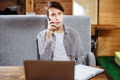 Young handsome man talking on the phone sitting in a cafe royalty free stock images