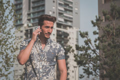 Young handsome man talking on phone in the street Stock Photos