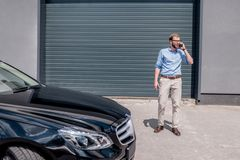 Young handsome man talking on smartphone and standing. Near the car Stock Photos