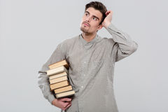 Young handsome man thinking and holding books Stock Photos