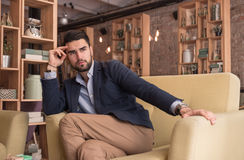 Young handsome man thinking looking cafe indoors. Young adult man handsome, looking, thinking indoors interior cafe sitting sofa stock images