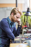 Young handsome man thinking while soldering a circuit board Stock Photo
