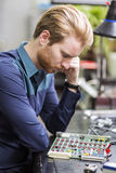 Young handsome man thinking while soldering a circuit board Royalty Free Stock Image