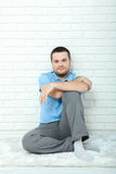 Young handsome man thought sitting on the floor near wall in living room. Attractive man with beard sitting at the white Stock Images