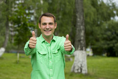 Young handsome man with thumb up in a green shirt on the backgro Royalty Free Stock Images