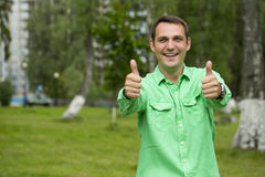 Young handsome man with thumb up in a green shirt on the backgro Stock Photos