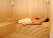 Young handsome man in a towel relaxing in sauna Stock Images
