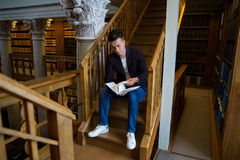 Young handsome man in traditional library. Young handsome man sitting on wooden stairs in traditional library, holding book. Beautiful interior of old library royalty free stock images