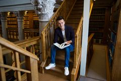 Young handsome man in traditional library. Young handsome man sitting on wooden stairs in traditional library, holding book. Beautiful interior of old library stock image