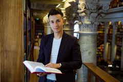 Young handsome man in traditional library. Young handsome man standing in traditional library at bookshelves, holding book. Beautiful interior of old library stock photo