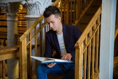 Young handsome man in traditional library. Young handsome man sitting on wooden stairs in traditional library, holding book. Beautiful interior of old library stock photography