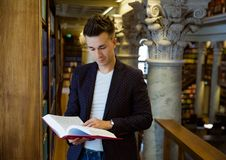 Young handsome man in traditional library. Young handsome man standing in traditional library at bookshelves, holding book. Beautiful interior of old library royalty free stock images