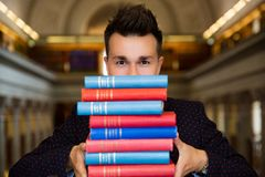 Young handsome man in traditional library. Young smiling handsome man standing in traditional library, holding pile of books. Beautiful interior of old library stock photo