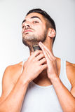 Young handsome man trimming his beard Stock Photography