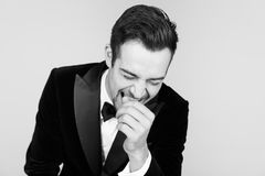 Young handsome man in a tuxedo, laughing, holding hand near fac. Portrait of a young handsome man in a tuxedo, laughing, holding hand near face, against pl royalty free stock images