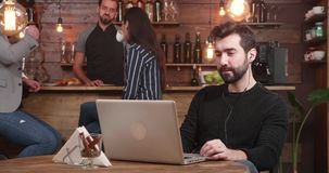 Young handsome man typing a message on his laptop while relaxing in a vintage coffee shop stock footage