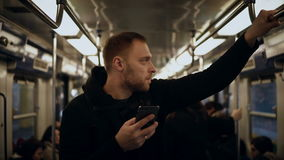 Young handsome man uses the smartphone in public transportation, in metro. Male surfing the Internet with touchscreen. Guy chatting in social network stock video footage