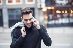 Young handsome man using his cell phone, enjoying a day on the street. Handsome man cell phone call smile outdoor city street, Young attractive businessman Stock Image