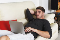 Young handsome man using his laptop Stock Images