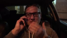 Young handsome man using mobile phone in the car. Young handsome man using mobile phone in his car stock video