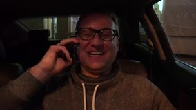 Young handsome man using mobile phone in the car. Young handsome man using mobile phone in his car stock video footage