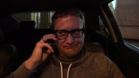 Young handsome man using mobile phone in the car. Young handsome man using mobile phone in his car stock footage