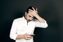Young handsome man using a mobile phone with a negative attitude. Young handsome man with beard and mustache using a mobile phone with a negative attitude Stock Photo