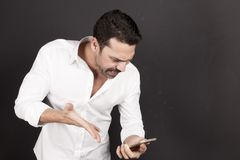Young handsome man using a mobile phone with a negative attitude. Young handsome man with beard and mustache using a mobile phone with a negative attitude Royalty Free Stock Image