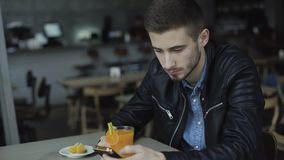 Young handsome man using smartphone in cafe 4K.  stock video footage
