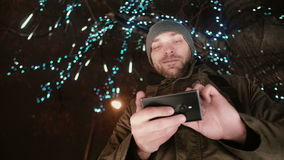 Young handsome man using smartphone at Christmas night standing under a tree decorated with sparkling lights. Portrait of a young handsome man in the falling stock video