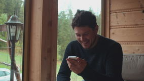 Young handsome man using smartphone at home. Cheerful young man relaxing on sofa and looking at his smartphone stock video