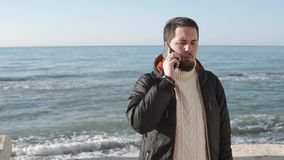 Adult man dressed in an autumn jacket, talking on his mobile phone near the sea. A young and handsome man is on a vacation by the sea, waves are beating against stock video footage