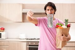 The young handsome man with vegetables in the kitchen royalty free stock images